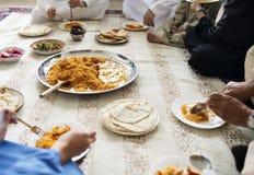 Muslimsk familj som har matställen på golvet royaltyfria bilder