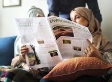 Muslimsk familj som läser nyheterna arkivbilder