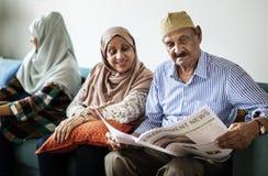 Muslimsk familj som läser nyheterna arkivfoto
