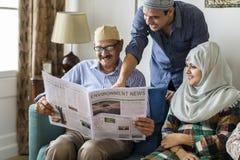 Muslimsk familj som läser nyheterna arkivbild