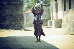 Muslimsk flicka för foto som barfota går på dervne med bagage på deras huvud som filmas i Madagascar i Oktober 2014 Arkivbild