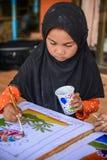 Muslimsk flicka med svart tyg för hijabmålningBatik Arkivfoton