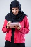 Muslimsk flicka som använder minnestavlan Arkivbilder