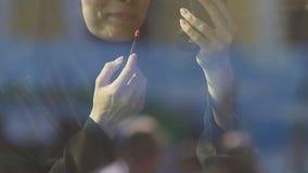 Muslimsk flicka som offentligt applicerar läppstift, förbud för islamiska kvinnor på skönhetsmedel arkivfilmer