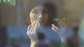 Muslimsk flicka som offentligt gör makeup i kafé, förbud för islamiska kvinnor på skönhetsmedel arkivfilmer