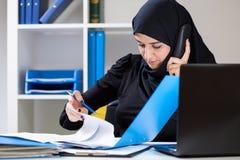 Muslimsk kontorsarbetare som söker efter dokumentet Arkivbilder