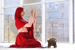 Muslimsk kvinna i hijab som inomhus ber på mattt arkivfoton