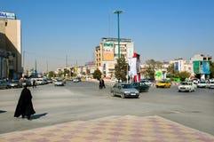 Muslimsk kvinna i traditionell hijabklänning som rusar på den upptagna stadsgatan med många bilar arkivfoton