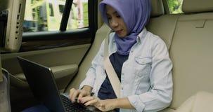 Muslimsk kvinna som använder bärbara datorn i bil stock video
