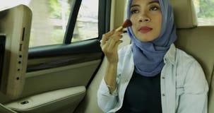 Muslimsk kvinna som applicerar makeup i bilen stock video