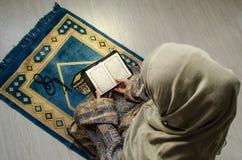 Muslimsk kvinna som ber för Allah muslimgud på rum nära fönster Händer av muslimkvinnan på mattan som ber i traditionellt bära Fotografering för Bildbyråer