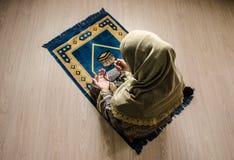 Muslimsk kvinna som ber för Allah muslimgud på rum nära fönster Händer av muslimkvinnan på mattan som ber i traditionellt bära Arkivfoton