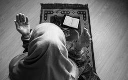Muslimsk kvinna som ber för Allah muslimgud på rum nära fönster Händer av muslimkvinnan på mattan som ber i traditionellt bära Royaltyfri Bild