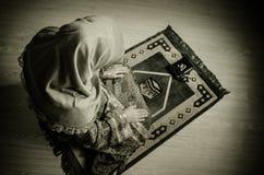 Muslimsk kvinna som ber för Allah muslimgud på rum nära fönster Händer av muslimkvinnan på mattan som ber i traditionellt bära Royaltyfri Fotografi