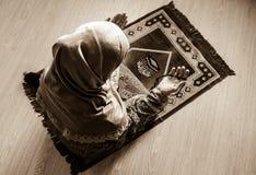 Muslimsk kvinna som ber för Allah muslimgud på rum nära fönster Händer av muslimkvinnan på mattan som ber i traditionellt bära Arkivfoto