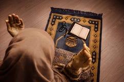 Muslimsk kvinna som ber för Allah muslimgud på rum nära fönster Händer av muslimkvinnan på mattan som ber i traditionellt bära Royaltyfri Foto