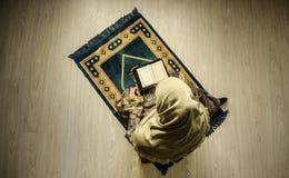 Muslimsk kvinna som ber för Allah muslimgud på rum nära fönster Händer av muslimkvinnan på mattan som ber i traditionellt bära Royaltyfria Foton
