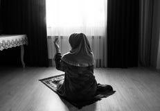 Muslimsk kvinna som ber för Allah muslimgud på rum nära fönster Händer av muslimkvinnan på mattan som ber i traditionellt bära Arkivbild