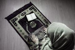 Muslimsk kvinna som ber för Allah muslimgud på rum nära fönster Händer av muslimkvinnan på mattan som ber i traditionellt bära Royaltyfria Bilder