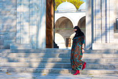 Muslimsk kvinna som går på marmortrappa av moskén Arkivbilder