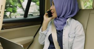 Muslimsk kvinna som gör en påringning i bil lager videofilmer