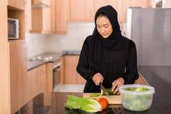 Muslimsk kvinna som hugger av grönsaker royaltyfria foton