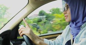 Muslimsk kvinna som kör bilen, medan sjunga arkivfilmer