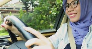 Muslimsk kvinna som kör bilen, medan sjunga lager videofilmer