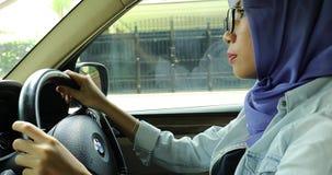 Muslimsk kvinna som kör en bil stock video