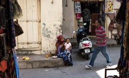 Muslimsk kvinna som matar hennes barn på zanzibar Arkivbilder