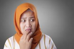 Muslimsk kvinna som oroas som är nervös och ser till sidan royaltyfri bild