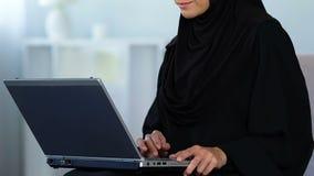 Muslimsk kvinna som skriver på bärbar datordatoren, arbeta som är hemmastatt som är frilans- eller utbildning arkivfilmer