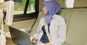 Muslimsk kvinna som sover i bil med bärbara datorn stock video