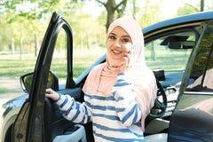 Muslimsk kvinna som talar på telefonen nära hennes bil arkivfoto