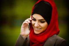 Muslimsk kvinna som talar på telefonen och använder teknologi Den muslimska kvinnan använder den smarta telefonen arkivfoton