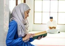 Muslimsk kvinnaläsning från quranen royaltyfria bilder