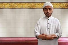 Muslimsk man som ber i moské Arkivfoton