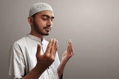 Muslimsk man som ber på grå bakgrund Royaltyfri Fotografi