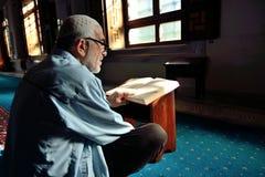 Muslimsk man som läser den heliga Qur'anen Arkivfoton