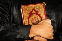 Muslimsk man som rymmer Koranen Fotografering för Bildbyråer