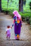 Muslimsk moder med hennes dotter på telantgården royaltyfri foto