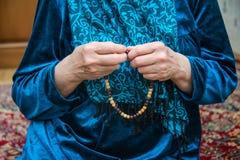 Muslimsk radband i händerna av en äldre kvinna arkivbilder