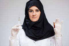 Muslimsk sjuksköterskainnehavinjektionsspruta Arkivbilder