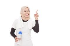 Muslimsk sportig kvinna som rymmer en flaska av mineralvatten medan poin Arkivbild