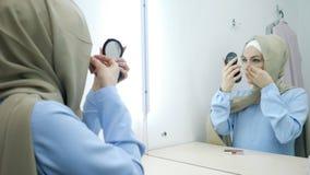 Muslimsk ung attraktiv kvinna i beige hijab och traditionella bl?a kl?nningen som g?r smink lager videofilmer