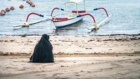 Muslimska kvinnor, i Abaya Niqab sammanträde och att koppla av stranden på havet Nusa Dua, Bali Fotografering för Bildbyråer