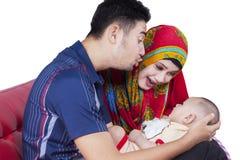 Muslimska par som spelar med gulligt, behandla som ett barn Royaltyfria Bilder