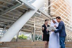 Muslimskt affärsman- och affärsfolk som ser till anteckningsboken och samtalet om affärsplan royaltyfri foto
