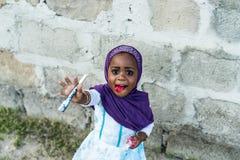 Muslimskt barn av zanzibar den bärande violetta burkaen Arkivbild