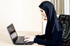Muslimskt kvinnasammanträde på en kontorsstol och arbete på datoren Arkivfoton